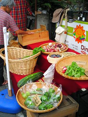 カフェの外側に並べられた新鮮な野菜たち。大きなザルや籠の中に、見慣れぬ野菜がずらりと並んでいます。ところどころ残り僅かなものも。お客さんが手にとって野菜を吟味しています。