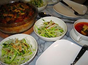 白い四角い取り分け皿、その隣に具沢山の赤いスープ、その向こうに白い丸い器に大根ときゅうりのサラダ、更にその向こうに透明の耐熱ガラスに入ったライスグラタンが。