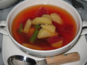白い両手持ちのスープカップに、野菜がゴロゴロの赤いスープが入っています。