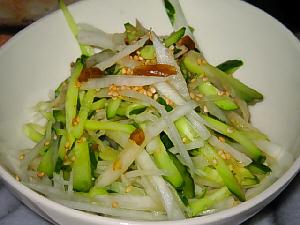 白い器に入ったサラダ。きゅうりと大根の千切り野菜にドレッシングと炒りゴマがかけられています。