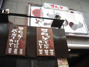 タココロッケを売っていたお店の入り口。看板にコロッケ:たこ、ぼっかけ、カレーと書かれ、3種類のコロッケを売っているのが解ります。そしてそれらを挟んだバーガーも。