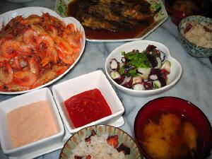 タコ飯の入ったご飯茶碗、味噌汁椀、それらの向こう側に、エビのソース2種類が入った小鉢、隣にタコのサラダ、更に向こうに白い大きなボウルに入った茹でエビ屋守り、その隣に小ぶりの煮付けた魚が入った大皿が並んでいます。