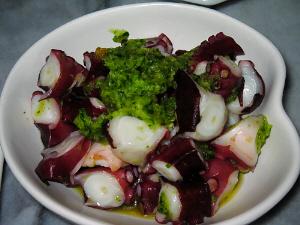 白いハート型の器に盛られたタコのサラダ。緑のきゅうりがアクセント。赤と緑の綺麗な一品。