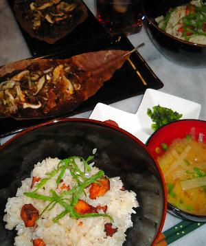 手前から、黒い丼にサケご飯、隣に青ネギが浮いた大根の味噌汁。その向こうに梅干とシソの実漬けの入った白いひし形が二つくっついたような小皿が、更にその向こうに、長方形の黒いお皿に乗った朴葉焼きが並んでいます。