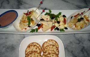 細長い白いお皿に盛り込まれた、チーズの盛り合わせと、パテ。手前にクラッカーが入ったお皿も見えています。