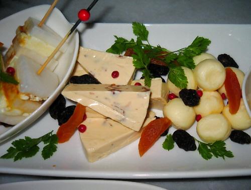 チーズ盛り合わせのアップ画像。まん丸ボール型のチーズに、三角形にカットされたラムレーズン入りのチーズ、そして小さな白い小鉢には、大根とチーズの重ねたものが、長めの楊枝に刺して盛られています。レーズンやドライフルーツ、そしてピンクペッパーがアクセントに散らしてあります。