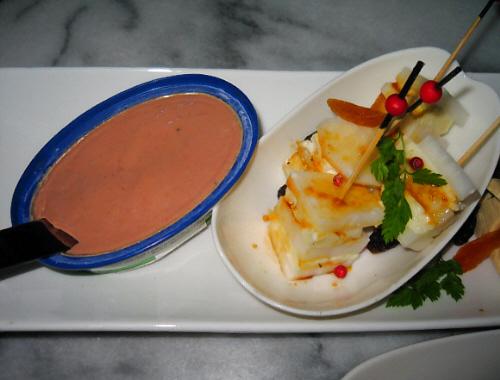 小さな缶に入ったフォアグラ入りのパテと、大根とチーズの串刺し。串の先端には赤い丸いボールがついていて、先が黒く塗られています。