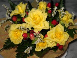 黄色いバラと真っ赤な木の実、白い小さな花がバランスよく盛り込まれたテーブルフラワー。