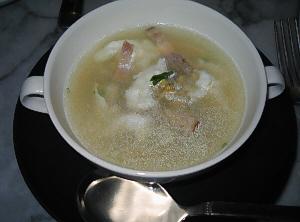 黒い丸皿の上に白い両手持ちのスープカップが。ベーコンと白っぽいものがスープから顔を覗かせています。
