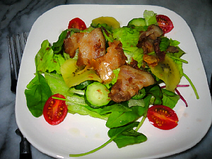 四角い白いお皿に盛られたサラダ。緑の葉、真っ赤なトマト、ベーコンのこんがり焼けた色合いが綺麗な一皿。