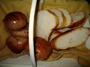白い木の籠の中に、ゴールドのランチョンマットが敷かれ、その上にパンが盛り込まれています。