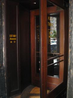 海外の古いホテルのような回転扉の入り口。回転扉はかなり大き目のもので、一つの区切りに大人が二人入っても、全く窮屈ではありません。かなり使い込まれたどっしりした回転扉です。昔ここは銀行でした。
