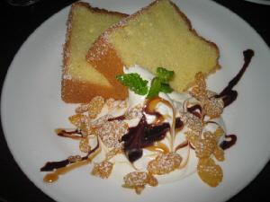 白い丸皿に盛られたシフォンケーキ二切れ。生クリームにチョコレートが少々アクセント付けされています。飾ったミントの葉が綺麗です。