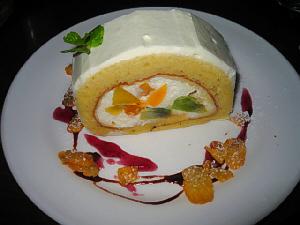 同じく白い丸皿に盛られたロールケーキ。ロールの中には、生クリームとフルーツがたっぷり。