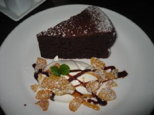 同じく白い丸皿に盛られたチョコレートケーキ。やはり生クリームが添えられています。