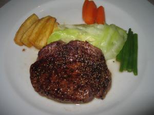 薄めのステーキ肉の入ったお皿。付け合せの野菜は、キャベツ、じゃが芋、人参、いんげん。100gちょっとくらい?。
