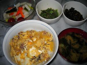親子丼と隣にわかめの味噌汁。向こう側にピクルスの入ったガラスの器、そして小さな白い鉢二つに、漬物が入っています。