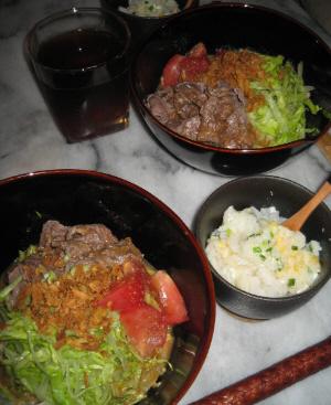 納豆ダレの冷やしうどんが入った黒い丼、隣には小さな黒っぽい器に雑炊が入っています。
