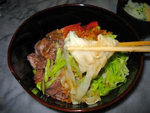 うどんを箸でつまみあげている写真。白いきし麺が黒い丼に映えて綺麗です。