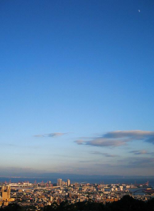 神戸の町並みの向こうに海が広がって、空は真っ青、そして白い三日月が見えます。