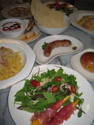 手前の白い丸皿にサラダが、その向こうに白い八角形のお皿にカルボナーラ、三日月のような変形のお皿にソーセージ、四角い白い小さめのお皿にクルミパン。それらの更に向こうに白いボウルに薄いパン。その隣にチーズが2種、そしてアスピック風のハムが一枚乗ったお皿が並んでいます。