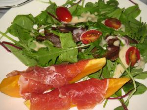 白い丸皿に盛られたサラダ。パパイヤの生ハム乗せが2本と、数種類のリーフのサラダにプチとマトの輪切りが散らしてあります。