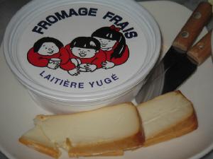白い容器に子供の顔が描いてあるフロマージフレと、チーズのカットしたものが乗った四角い白いお皿。木の柄の付いた小さなバターナイフが2つ添えられてあります。