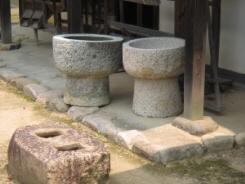 石の臼のようなもが二つ並んでいます。手前には何かの器具の土台だった穴が二つ開いた四角い石も見えます。