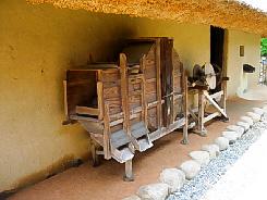 古い脱穀機のような木の器具。軒下に置かれてあります。