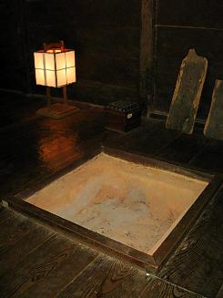 黒光りした囲炉裏の周りの木の床。四角い囲炉裏の向こうに行灯が置かれてあります。線香で時を計る四角い時計も見えます。