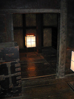 寝室に使われていたのか、奥座敷。屈んで入らないといけない大きさの入り口が開いています。壁も床も黒光りした板張り。年季が入っているのが解りますね。