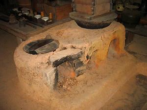 かなり旧式なかまど。火を炊く部分が二つ。一方にはやっぱり相当古いタイプのお釜と蒸し器が乗せられています。