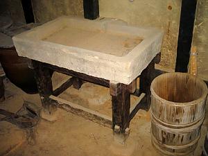 簡素でも丈夫な木の土台の上に乗せられた石の流し。脇には大きめの壷と、桶が置かれてあります。