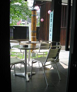 カフェの中から外を撮った一枚。アルミのテーブルと椅子が配置されていて、小さな庭の木々に提灯が下げられています。夜は灯りが点るのでしょう。