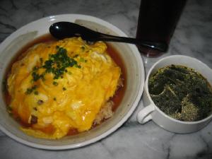 和風の丸皿に盛られた天津飯。黒いほっそりしたスプーンが添えられてあります。白い両手持ちのカップスープにはわかめスープが。