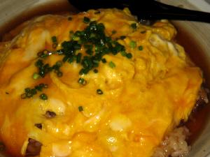 天津飯のアップ画像。黄色い玉子とちょっと濃い目の色合いの餡。緑のネギのトッピングがアクセント。