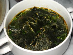 うっすらと赤いものが浮いているわかめスープ。ラー油の赤です。ゴマとネギを散らしてアクセントに。