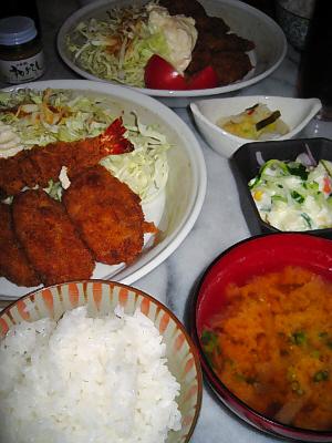 ご飯、味噌汁、フライの盛り合わせ、四角い黒い器にポテトサラダ、舟形の小さな白い器に漬物が入っています。