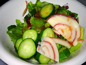 白い小さめのボウルに盛られたサラダ。色々な葉ときゅうり、そして白っぽいチーズがアクセントになったサラダ。