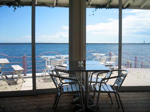カフェの大きな窓から海を臨んだ一枚。テラスの白いデッキチェアーと白い軒先、淡い紫色の手摺、そして広がる青い海。エーゲ海でも眺めている雰囲気が漂うカフェです。