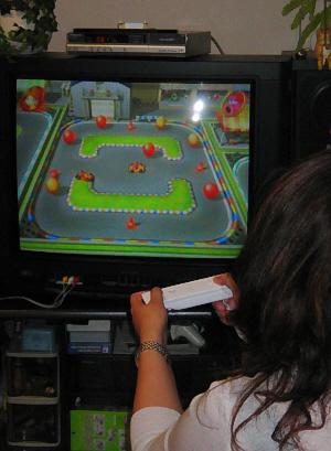 TV画面に向かって、必死でリモコンを操作する若い女性の後姿。