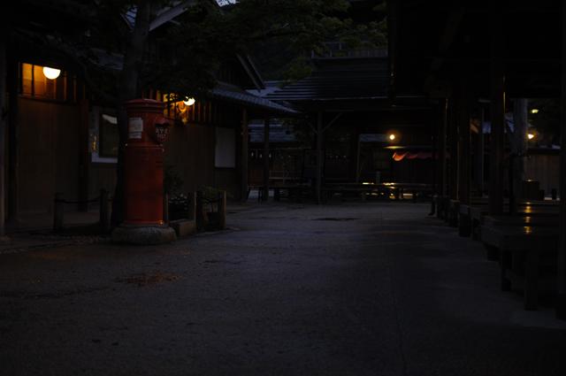 ちょっと観光地化したような感じもありましたが、日も暮れ人通りはほとんどありませんでした。昼間なら賑やかそうな神社前の休憩所で少し腰をおろして休憩です。古い建物からは電球の明かりがもれ、暗い通りには昔ながらの赤いポストがあります。奥には小さな神社がうっすらと見える程度でとても静かな街並みです。