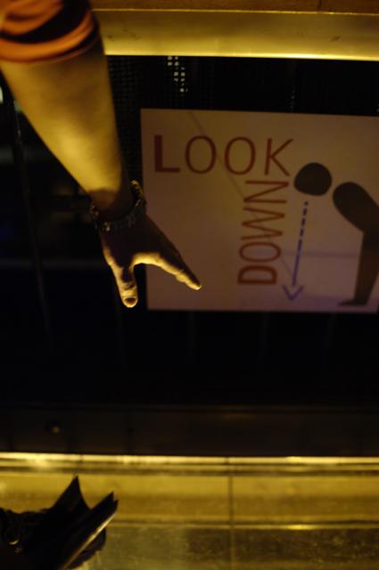 東京タワーに昇ると、展望台のデッキの床がガラスになっており、下を見て♪と看板がありました。友達が指をさしている様子が写っています。