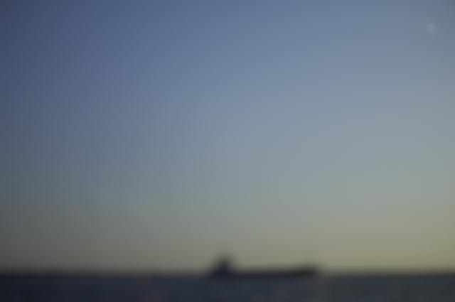 カフェの窓辺の席から二、三歩進むとそこは海です。夕日がさすこの席から海を走る大きな船をぼかして撮ってます。海と船と空の境目がボヤっとしていて、自分のイメージでは夢を起きてから思い出した時の風景です。