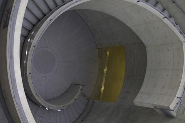 螺旋階段を上りきり、上から下を撮っています。螺旋といっても、円い筒状の真ん中が吹き抜けになっていて、筒の外側に階段がグルグル回っているコンクリート製の階段です。ここを小さいラッキー君が走っていたのですが、写真には階段だけ写っています。