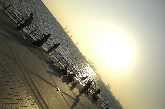 海辺には釣り人や海に向かって絵かなんかをしている人達でいっぱいです。夕日が海に反射して眩しいくらいの夕日と海辺の人々です。