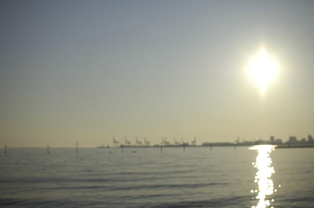 湾曲している砂浜の奥には大きいクレーン(キリンさんに見えます)が並び夕日が海を照らし光がこちらになびいてる感じです。またまたぼかして撮ってます♪。