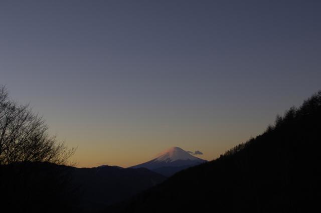 山梨県の柳沢峠からの初日の出。望遠レンズではないので周りの山も写っていますが富士山山頂が朝日に照らされています。