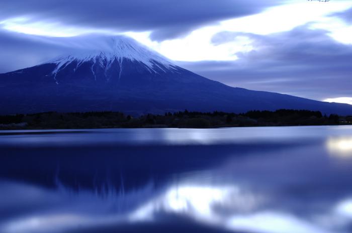 太陽さんが昇る1時間ほど前の富士山です。全体に明るい青色に包まれ湖面には逆さ富士があり、雲の切れ間からは光が差し込んでいるような雰囲気です。