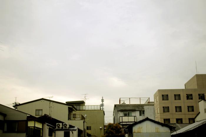 京都の小道を歩いて少し大きめの駐車場から家並みと空を撮ってみました。古いけどコンクリート造りの家です。